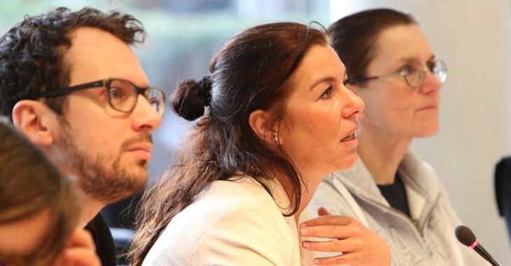 Foto von Lisa Yashodhara Haller, am Podium zwischen anderen Personen