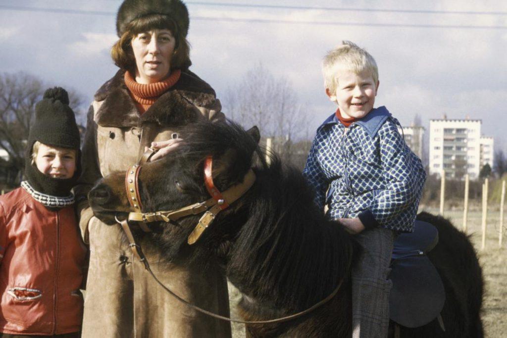 Foto von Frau mit 2 Kindern, eins davon auf einem Pony